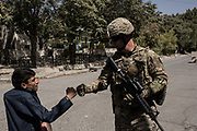 KABUL, AFGHANISTAN - SEPTEMBER 6: United States Air Force Major John Ross greets a local Afghan on the way to a public affairs advising mission with the Afghan Ministry of Defense on September 6, 2017 in Kabul, Afghanistan. Currently the United States has about 11,000 troops in the deployed in Afghanistan, with a reported 4,000 more expected to arrive in the coming weeks. Last month, President Donald Trump announced his plan for Afghanistan which called for an increase in troop numbers and a new conditions-based approach to the war, getting rid of a timetable for the withdrawal of American forces in the country. (Photo by Andrew Renneisen/Getty Images)
