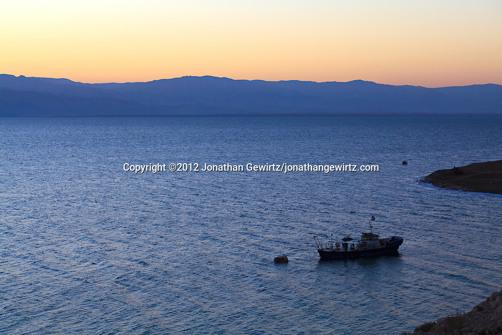 A boat lies at anchor near the public beach at Ein Gedi on the western coast of the Dead Sea shortly before sunrise. WATERMARKS WILL NOT APPEAR ON PRINTS OR LICENSED IMAGES.