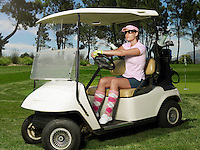 Young female golfer in sitting in cart