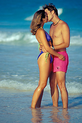 A young couple kiss on the beach in Bermuda. (model released)