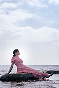 a woman in a pink dress is sitting on stones at the sea
