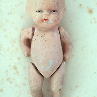 Vintage bisque naked baby doll showing scratches and signs of wear lying on antique paper