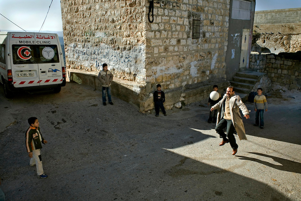 A mobile clinic from the Palestinian Medical Relief Center (PMRC) visits a small village called Far'ata. The driver of the van takes a few minutes to play ball with local kids...Photo: Markus Marcetic/MOMENT