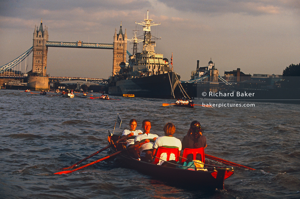 Facing a setting sun, the near-exhausted rowers of a small 'jolly boat' has almost completed the long Great River Race by pulling their oars along 22 miles of the River Thames. About to row past the battleship HMS Belfast on the right and under Tower Bridge beyond, the four friends negotiate the choppy waters of the capital's river. The Great River Race (also known as 'London's River Marathon') attracts both the true racer and the leisure rower. The course from Richmond to London docklands was inspired by the immense interest generated by a 1987 charity event in which the famous Doggett's Coat & Badge winners from The Company of Watermen & Lightermen rowed its shallop, or passenger barge, from Hampton Court to The Tower of London.