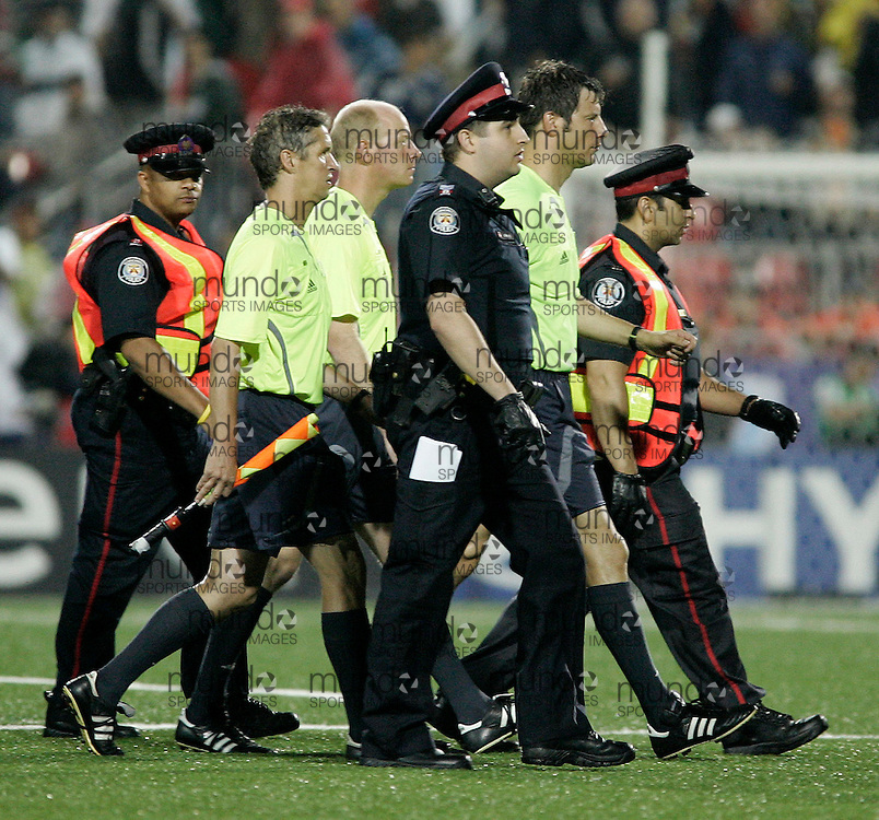 The officials are escorted off the field by Toronto Police following the controversial semi-final match between Chile and Argentina at the FIFA U-20 World Cup on 19 July 2007 in Toronto, Ontario, Canada.  Argentina eliminated Chile with a 3-0 win..AFP PHOTO/GEOFF ROBINS