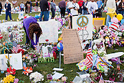 "15 JANUARY 2011 - TUCSON, AZ: A woman places a marker on the memorial on the lawn in front of the University Medical Center in Tucson, AZ, Saturday, January 15. The memorial has been growing since the mass shooting last week. Six people were killed and 14 injured in the shooting spree at a ""Congress on Your Corner"" event hosted by Congresswoman Gabrielle Giffords at a Safeway grocery store in north Tucson on January 8. Congresswoman Giffords, the intended target of the attack, was shot in the head and seriously injured in the attack. She is hospitalized at UMC. The alleged gunman, Jared Lee Loughner, was wrestled to the ground by bystanders when he stopped shooting to reload the Glock 19 semi-automatic pistol. Loughner is currently in federal custody at a medium security prison near Phoenix.  Photo by Jack Kurtz"