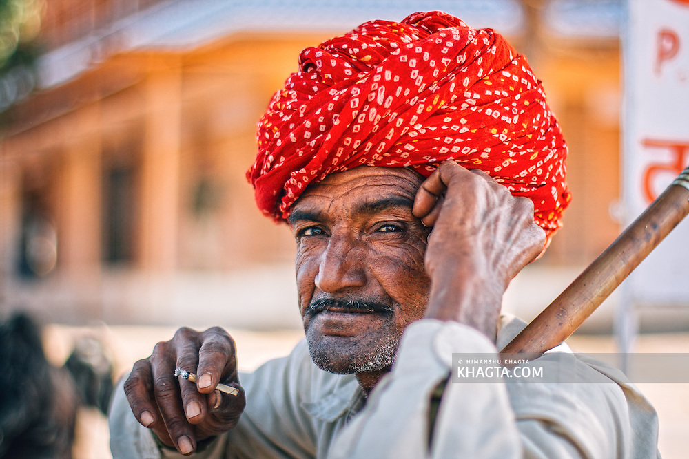 Portrait of Rajasthani man wearing a red turban smoking in Osian, Jodhpur