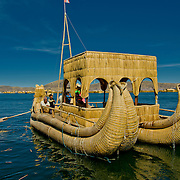 Reed boats of the Uros Islands (Islas Uros) ply the calm waters of lake Titicaca, Peru.