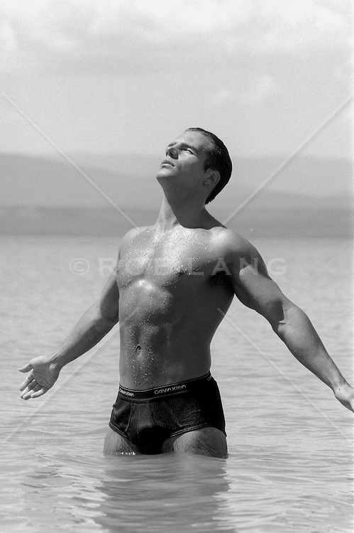 handsome man standing in a lake in his underwear enjoying the feel of the water and air
