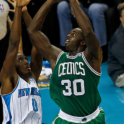 December 28, 2011; New Orleans, LA, USA; Boston Celtics power forward Brandon Bass (30) shoots over New Orleans Hornets small forward Al-Farouq Aminu (0) during the fourth quarter of a game at the New Orleans Arena. The Hornets defeated the Celtics 97-78.  Mandatory Credit: Derick E. Hingle-US PRESSWIRE