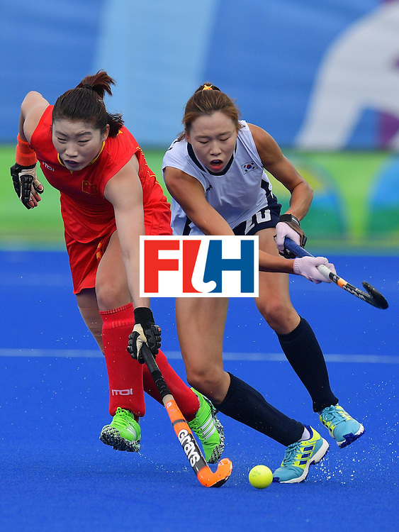 South Korea's Kim Hyunji (R) and China's Ou Zixia during the womens's field hockey South Korea vs China match of the Rio 2016 Olympics Games at the Olympic Hockey Centre in Rio de Janeiro on August, 12 2016. / AFP / Carl DE SOUZA        (Photo credit should read CARL DE SOUZA/AFP/Getty Images)
