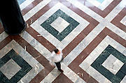male figure walking on marble tiles