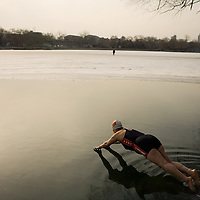 A Chinese woman dives in to her daily winter swim in the frozen lake of Ho-Hai, Beijing China. 22 January 2008. Winter swimmers believe in the health benefits of their daily ritual, an activity which claims to temper the body and increase energy levels. Photo: Bernardo De Niz