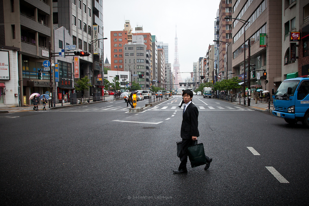 Japan Tokyo - A salary man cross the road in front of Tokyo tower lost in the clouds - 2012