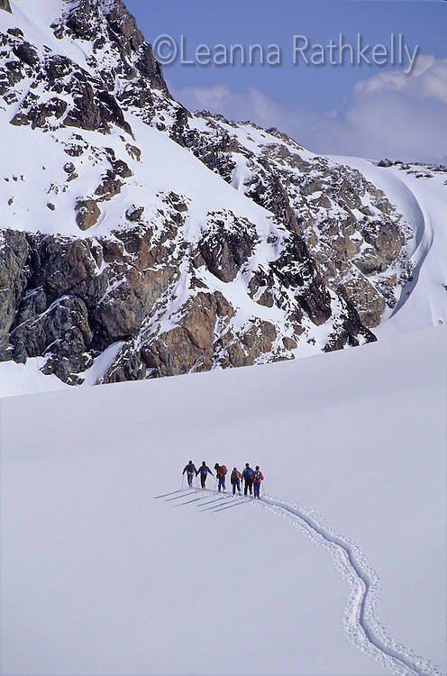 A group of people cross an icefield during a ski tour on the Pemberton Ice Cap, near Whistler, BC Canada