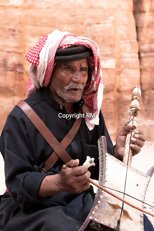 A musician playing a string instrument in the ancient city of Petra the capital city of Nabataeans famous for its water system and rock- cut architecture and an UNESCO World Heritage site also know as the Rose City due to the color of stone located in Jordan.