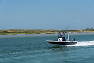 A sport fishing boat carrying two men with fishing rods boating out toward Cape Lookout National Seashore on the Crystal Coast and outer banks of North Carolina