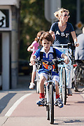 Een jongetje is met de fiets op weg naar de sportclub.<br /> <br /> A boy is cycling to the sports club.