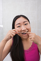 Portrait of young woman flossing her teeth in bathroom