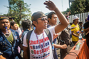 "01 FEBRUARY 2014 - BANGKOK, THAILAND:  Anti-government protestors taunt voters who tried to get past them to vote. The anti-government protestors also had guns and threatened to shoot people who wanted to vote. Thais went to the polls in a ""snap election"" Sunday called in December after Prime Minister Yingluck Shinawatra dissolved the parliament in the face of large anti-government protests in Bangkok. The anti-government opposition, led by the People's Democratic Reform Committee (PDRC), called for a boycott of the election and threatened to disrupt voting. Many polling places in Bangkok were closed by protestors who blocked access to the polls or distribution of ballots. The result of the election are likely to be contested in the Thai Constitutional Court and may be invalidated because there won't be quorum in the Thai parliament.   PHOTO BY JACK KURTZ"