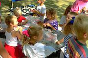 Kids age 3-7 working on 4H clay art project at Minnesota State Fair.  St Paul Minnesota USA
