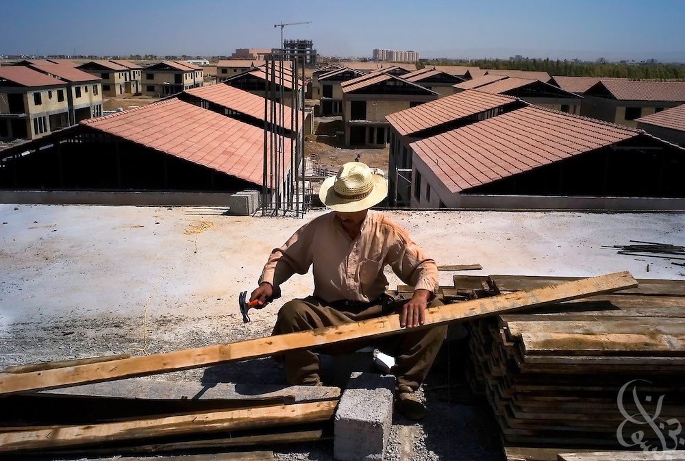 A Kurdish construction worker builds new houses at the English Village, a 410 unit residential housing complex May 22, 2007 in Erbil, Iraq. This joint private Iraqi/British investment project is just one of several large scale housing complex developments that are underway within Kurdistan as local government agencies have stepped up efforts to attract investment projects for the region.