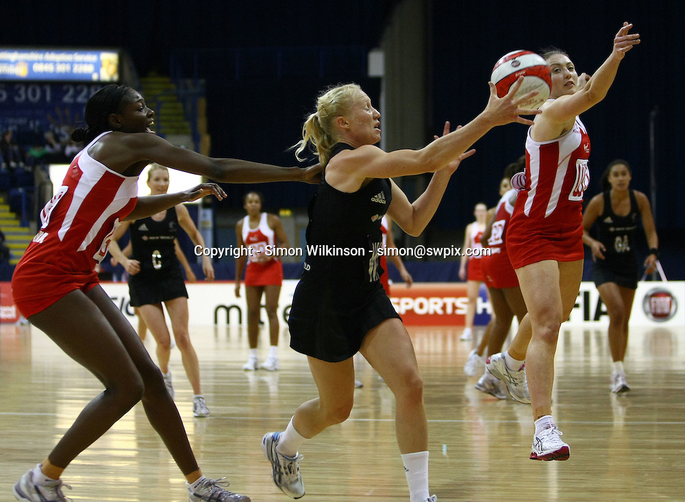 PICTURE BY VAUGHN RIDLEY/SWPIX.COM...Netball - International Netball Series - England v New Zealand - Capital FM Arena, Nottingham, England - 17/01/11...New Zealand's Laura Langman beats England's Sonia Mkoloma and Jade Clarke to the ball.