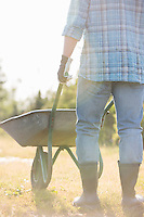 Low section rear view of man pushing wheelbarrow at garden