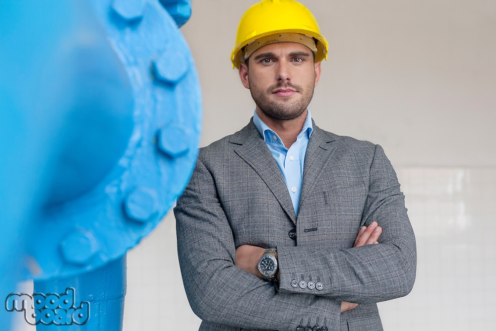 Portrait of confident young male architect standing arms crossed in industry