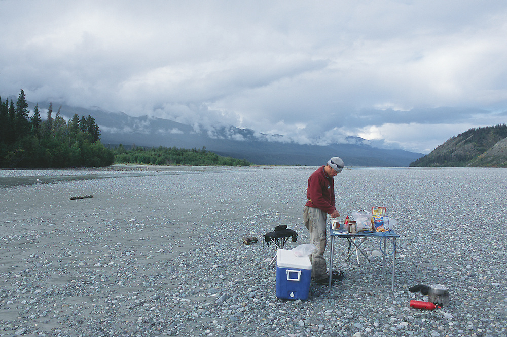 River guide serves lunch on folding table on flats of Chitina River in Wrangell-St. Elias National Park in Southcentral Alaska.  Fall.  Afternoon.