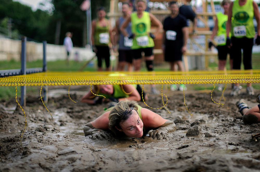 Jennifer Bookbinder of Howell crawls her way through the mud-drenched course during the Rock Solid Mud Run held at Old Bridge Township Raceway Park in Englishtown on August 6. Rock Solid Mud Run is an all-terrain adventure that involves mastering obstacles along either a five or ten-mile course. Participants ran, swam, crawled, climbed, jumped while covering four motocross tracks, hundreds of acres of woods, three lakes, and two asphalt racetracks.