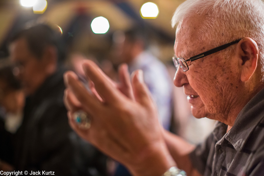 "12 JULY 2012 - FT DEFIANCE, AZ: A man prays during alter call at the 23rd annual Navajo Nation Camp Meeting in Ft. Defiance, north of Window Rock, AZ, on the Navajo reservation. Preachers from across the Navajo Nation, and the western US, come to Navajo Nation Camp Meeting to preach an evangelical form of Christianity. Evangelical Christians make up a growing part of the reservation - there are now more than a hundred camp meetings and tent revivals on the reservation every year. The camp meeting in Ft. Defiance draws nearly 200 people each night of its six day run. Many of the attendees convert to evangelical Christianity from traditional Navajo beliefs, Catholicism or Mormonism. ""Camp meetings"" are a form of Protestant Christian religious services originating in Britain and once common in rural parts of the United States. People would travel a great distance to a particular site to camp out, listen to itinerant preachers, and pray. This suited the rural life, before cars and highways were common, because rural areas often lacked traditional churches.   PHOTO BY JACK KURTZ"