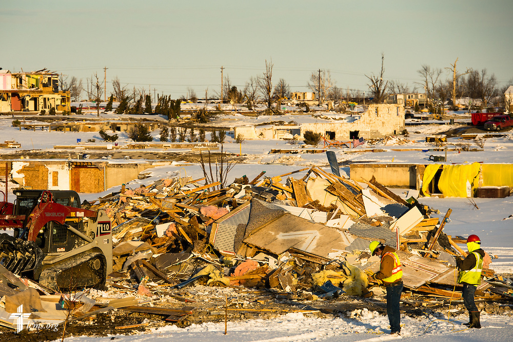Workers gather near the rubble of a home in a damaged neighborhood of Washington, Ill., on Wednesday, Dec. 18, 2013. Nearly two dozen tornadoes plowed through Illinois in November, killing a total of seven. LCMS Communications/Erik M. Lunsford