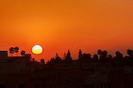 Sunset with palm silhouettes at the Place Jemaa el-Fna in Marrakech.
