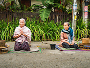 "11 MARCH 2016 - LUANG PRABANG, LAOS:  Lao women wait for Buddhist monks to pass him during the morning tak bat in Luang Prabang. Luang Prabang was named a UNESCO World Heritage Site in 1995. The move saved the city's colonial architecture but the explosion of mass tourism has taken a toll on the city's soul. According to one recent study, a small plot of land that sold for $8,000 three years ago now goes for $120,000. Many longtime residents are selling their homes and moving to small developments around the city. The old homes are then converted to guesthouses, restaurants and spas. The city is famous for the morning ""tak bat,"" or monks' morning alms rounds. Every morning hundreds of Buddhist monks come out before dawn and walk in a silent procession through the city accepting alms from residents. Now, most of the people presenting alms to the monks are tourists, since so many Lao people have moved outside of the city center. About 50,000 people are thought to live in the Luang Prabang area, the city received more than 530,000 tourists in 2014.      PHOTO BY JACK KURTZ"