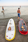 Stand up paddle boarders on the beach on Sullivan's Island, SC.