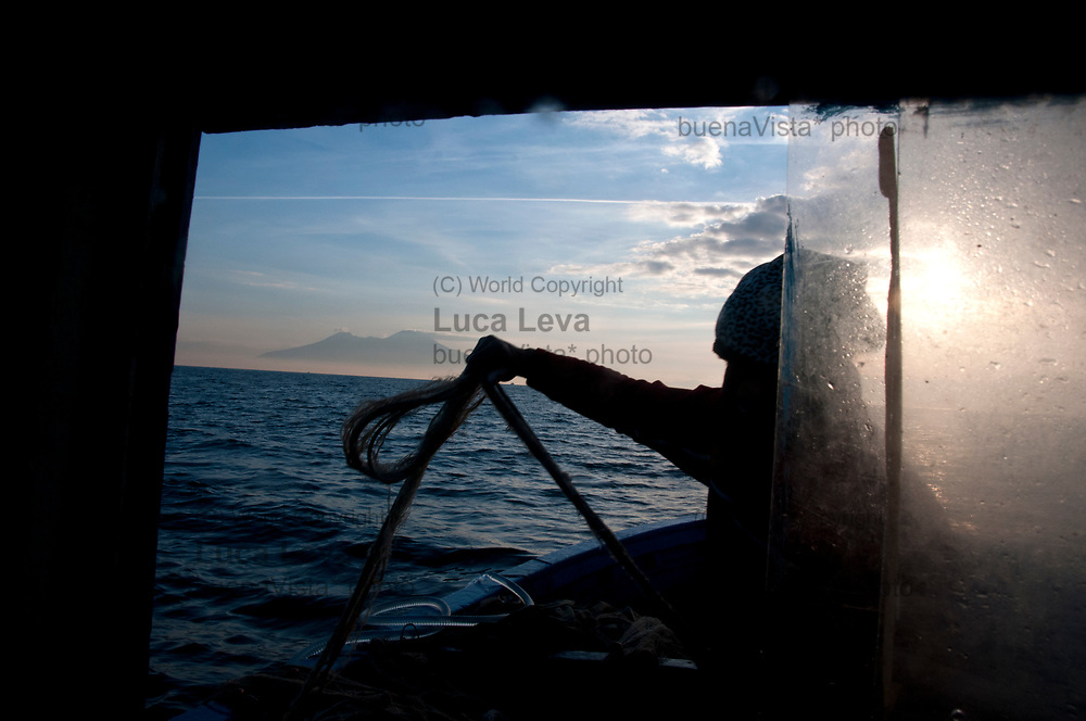 pescatore scioglie i nodi della rete da pesca all&rsquo;alba;<br />