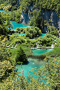 Visitors crowd boardwalks in the Lower Lakes (Donje jezera), in Plitvice Lakes National Park (Nacionalni park Plitvicka jezera, in Croatia, Europe), which was founded in 1949 and is honored by UNESCO as World Heritage Site. Waters flowing over limestone, dolomite, and chalk in this karstic landscape have, over thousands of years, deposited travertine barriers, creating natural dams, beautiful emerald lakes and waterfalls. Warming conditions after the last Ice Age (less than 12,000 years ago) allowed the natural dams to form from tufa (calcium carbonate) and chalk depositing in layers, bound by plants. Plitvicka Jezera is a municipality of Lika-Senj County, in the Republic of Croatia.