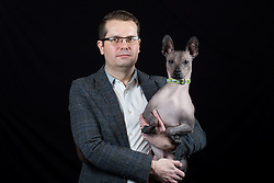 © Licensed to London News Pictures. 10/03/2016. Birmingham, UK. Tony Bolland with his Mexican Hairless dog named Schlitzie at Crufts 2016 held at the NEC in Birmingham, West Midlands, UK. The world's largest dog show, Crufts is this year celebrating it's 125th anniversary. The annual event is organised and hosted by the Kennel Club and has been running since 1891. Photo credit : Ian Hinchliffe/LNP