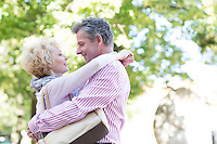 Side view of middle-aged couple embracing while looking at each other in park