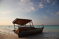 A traditional dhow boat sits on the beach in the Zanzibar archipelago, Tanzania.