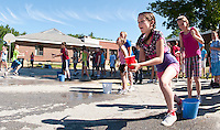 5th grader Kaitlynn Mize makes a mad dash for her team during the Tea Party Relay at Elm Street School's Alice in Wonderland themed Field Day Tuesday morning.  (Karen Bobotas/for the Laconia Daily Sun)