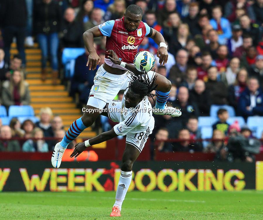 21st March 2015 - Barclays Premier League - Aston Villa v Swansea City - Jores Okore of Aston Villa beats Bafetimbi Gomis of Swansea City in the air - Photo: Paul Roberts / Offside.