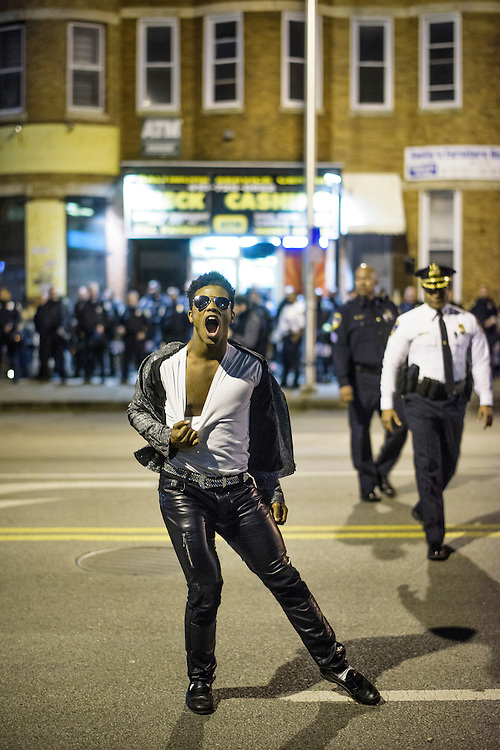 Baltimore, Maryland - April 30, 2015: For the past week Dimitri Reeves, a Baltimore-based Michael Jackson tribute performer, and recording artist, has been dancing for protestors and police in the riot-stricken areas of West Baltimore. Here he strikes a pose at the intersection of North and Pennsylvania Avenues, one of the riot's epicenters, in front of a police line, less than 30 minutes before the city's 10PM curfew Thursday night. <br /> <br /> CREDIT: Matt Roth