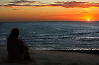 woman looking at sunset the big sand dune main attraction of the beautiful fisherman village of Jericoacoara in ceara state brazil