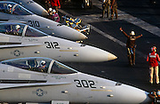 Red shirted ordnance men organise the busy deck of F/A-18C fighter jets on aircraft carrier on deck of USS Harry S Truman. The Truman is the largest and newest of the US Navy's fleet of new generation carriers, a 97,000 ton floating city with a crew of 5,137, 650 are women.