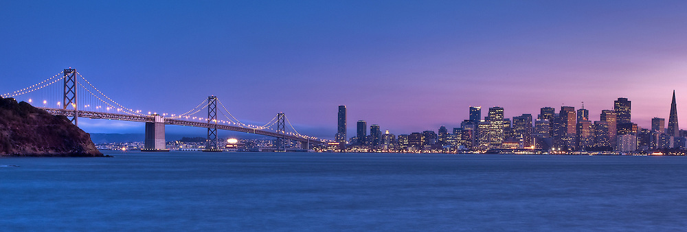 san francisco city skyline and the bay bridge at dusk from treasure island, panoramic shot.