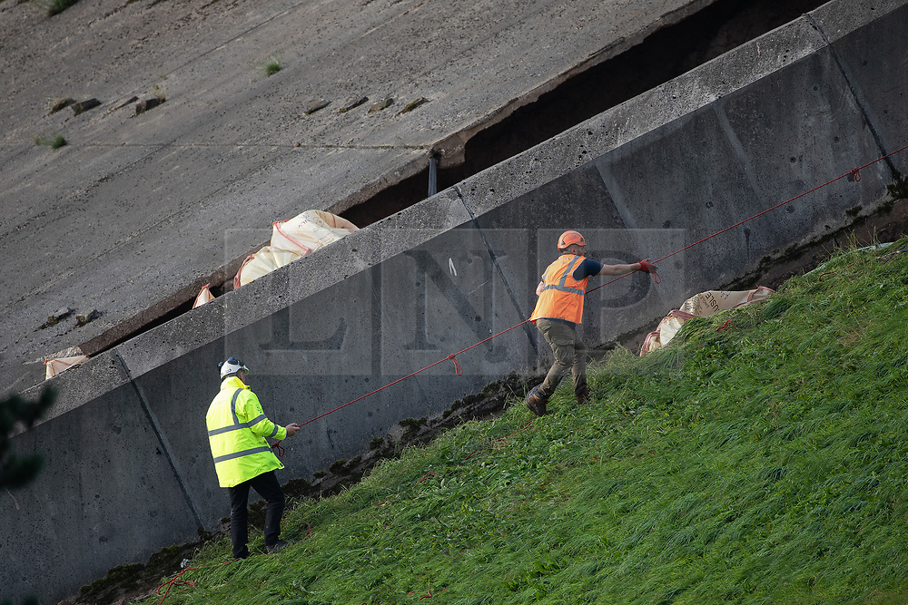© Licensed to London News Pictures. 03/08/2019. Whaley Bridge, UK. Bags of cement are manually mixed in wheelie bins before being carried down the side of the reservoir to reinforce the side of the slipway . The town of Whaley Bridge in Derbyshire remains evacuated after heavy rain caused damage to the Toddbrook Reservoir , threatening homes and businesses with flooding. Photo credit: Joel Goodman/LNP