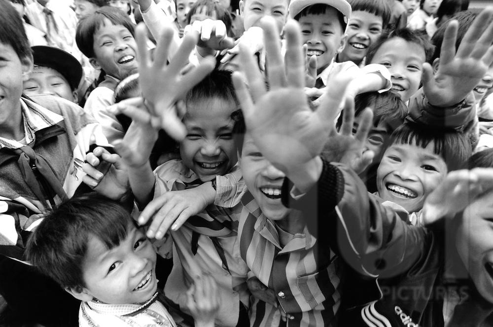 Vietnamese kids after school laugh and smile in front of the camera. Photo N/B, des enfants d'Hanoi tendent leurs bras pour dire bonjour (1995)