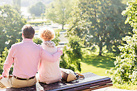 Back view of middle-aged couple relaxing on park bench